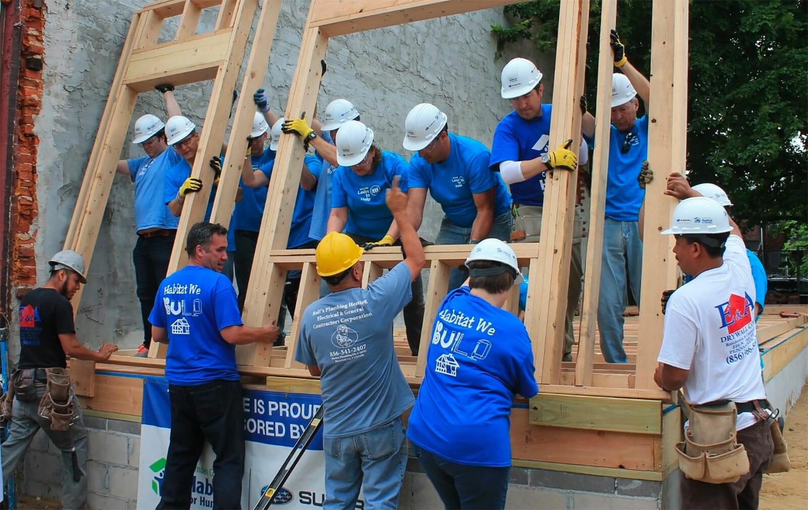 Volunteers raising wall of new home